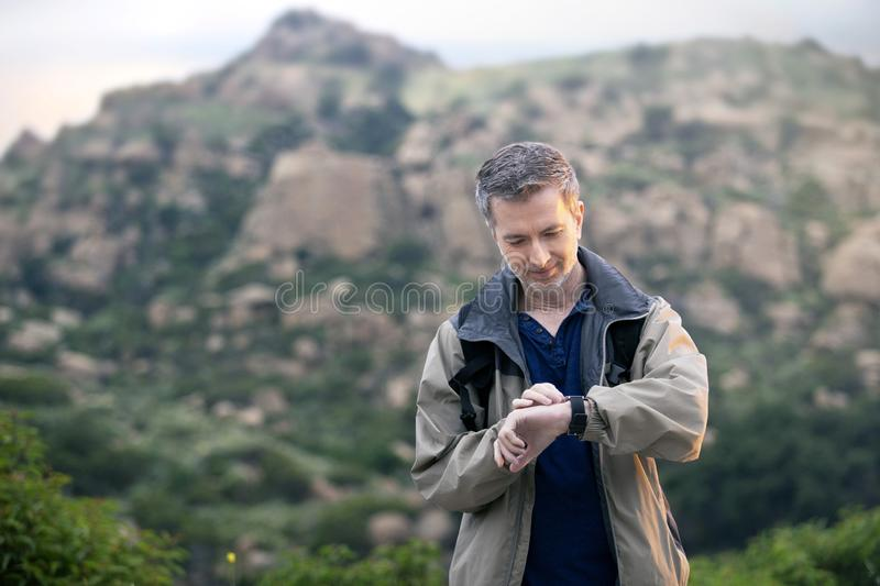 Man Enjoying Nature While Hiking on Vacation. Middle aged man staying healthy by doing outdoor activities during a nature getaway vacation.  He is hiking through stock image