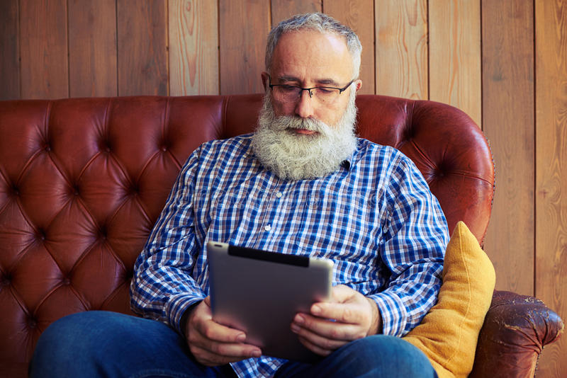Middle-aged man with tablet pc. Thoughtful middle-aged man with tablet pc resting on sofa at home royalty free stock photography