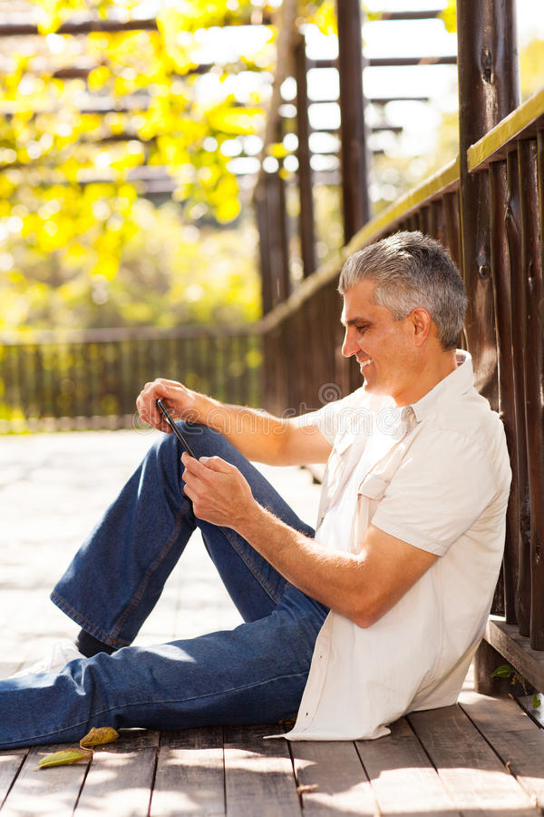 Middle aged man tablet stock photography