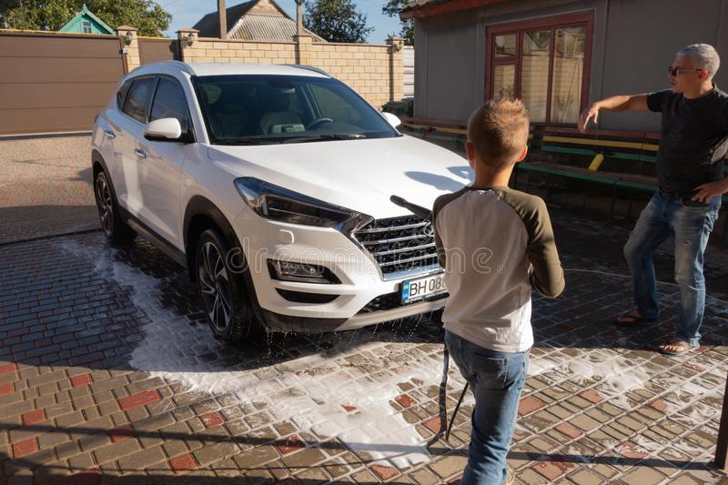 A middle-aged man teaches children of boys 4 and 10 years old to wash a car in the yard of his house on a summer sunny day. 2019. 09.22. Odessa. Ukraine royalty free stock images