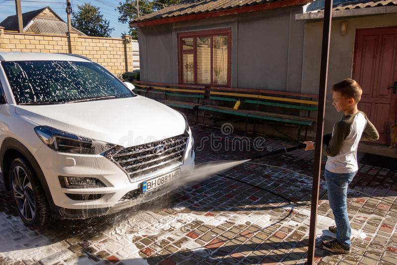A middle-aged man teaches children of boys 4 and 10 years old to wash a car in the yard of his house on a summer sunny day. 2019. 09.22. Odessa. Ukraine royalty free stock image
