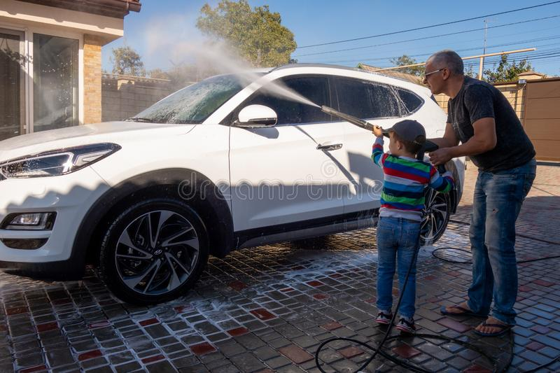 A middle-aged man teaches children of boys 4 and 10 years old to wash a car in the yard of his house on a summer sunny day. 2019. 09.22. Odessa. Ukraine stock image