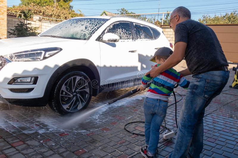 A middle-aged man teaches children of boys 4 and 10 years old to wash a car in the yard of his house on a summer sunny day. 2019. 09.22. Odessa. Ukraine stock photo