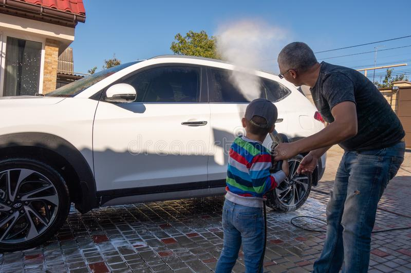 A middle-aged man teaches children of boys 4 and 10 years old to wash a car in the yard of his house on a summer sunny day. 2019. 09.22. Odessa. Ukraine royalty free stock photos