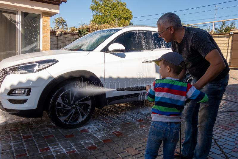 A middle-aged man teaches children of boys 4 and 10 years old to wash a car in the yard of his house on a summer sunny day. 2019. 09.22. Odessa. Ukraine stock images