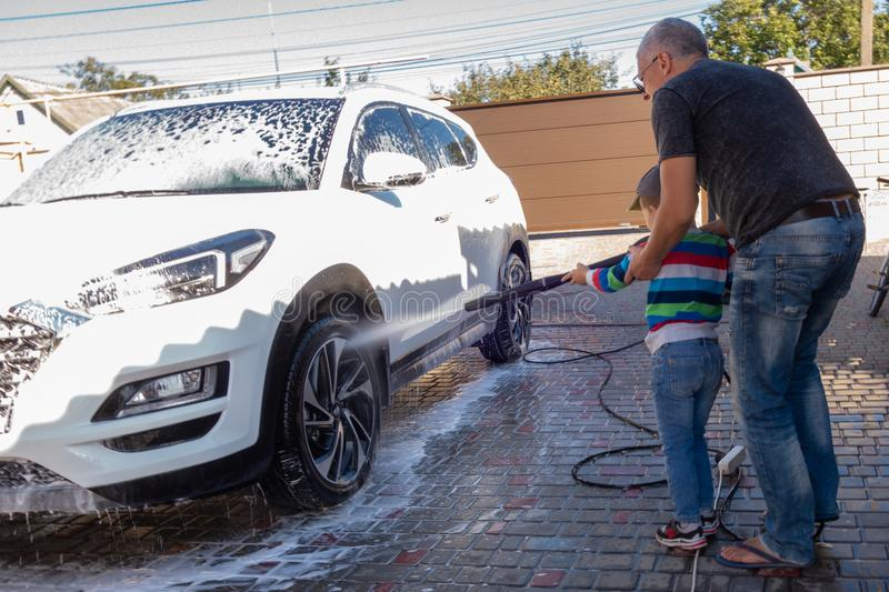 A middle-aged man teaches children of boys 4 and 10 years old to wash a car in the yard of his house on a summer sunny day. 2019. 09.22. Odessa. Ukraine stock photos
