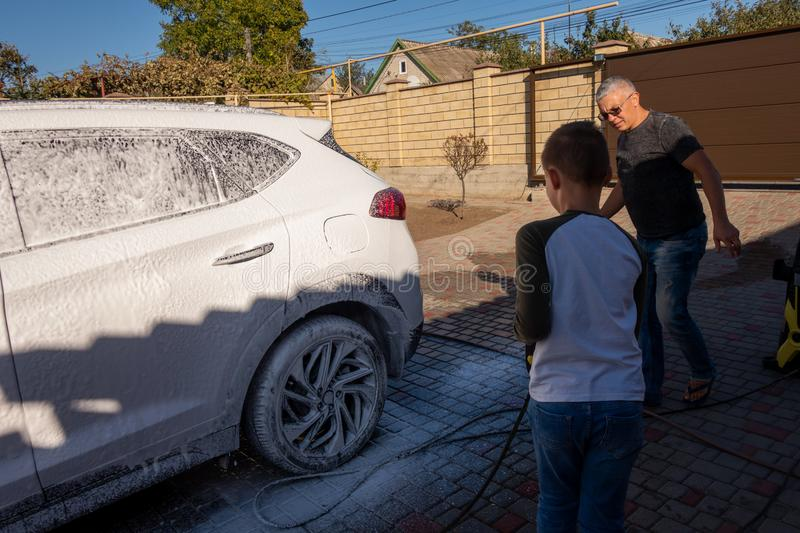 A middle-aged man teaches children of boys 4 and 10 years old to wash a car in the yard of his house on a summer sunny day. 2019. 09.22. Odessa. Ukraine royalty free stock photo