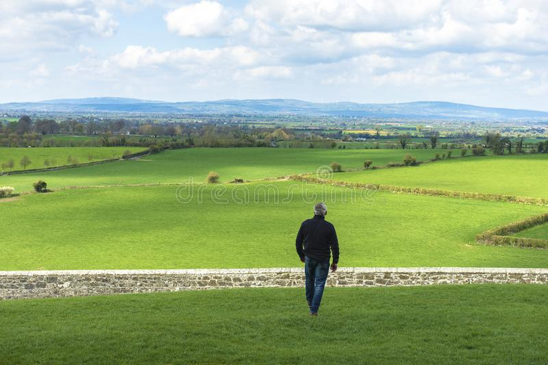 Middle-aged man walking in the field about to jump a wall, a stone fence. Overcome difficulties. Walk facing towards stock photos