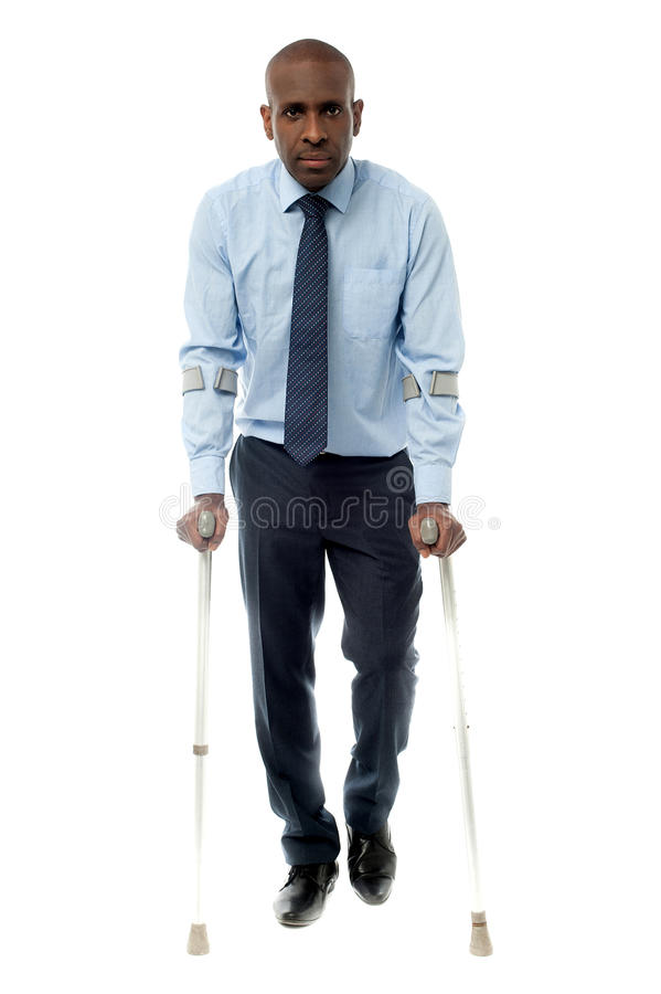 Middle aged man walking with two crutches stock images