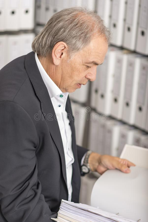 Middle-aged man is standing in front of a shelf wall with documents. Middle-aged man with white shirt is standing in front of a shelf wall with documents royalty free stock photo