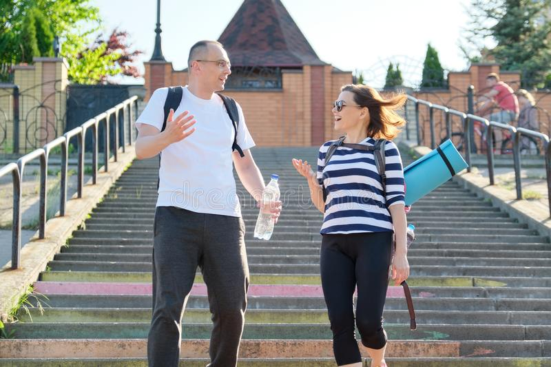 Middle-aged man and woman in sportswear talking walking royalty free stock photography