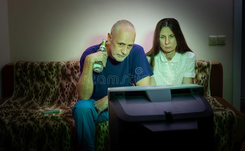 Middle-aged man and woman, watch television, looking sad, sitting on a couch stock photo