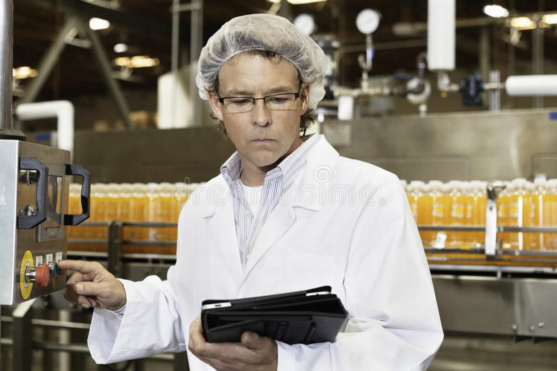Middle-aged man working in a bottling factory. Middle-aged men working in a bottling factory stock photo