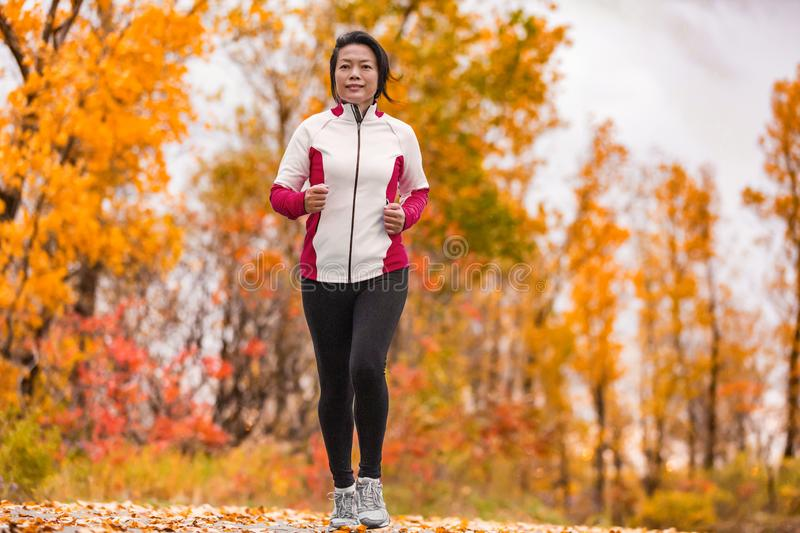 Middle aged mature woman running healthy lifestyle. Middle aged mature Asian woman running healthy lifestyle Chinese lady jogging in fall park in her 50s. Middle stock photos