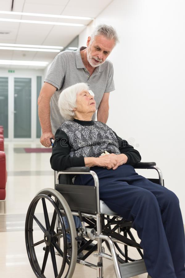 Middle aged man helping and taking to elderly 95 years old woman sitting in the wheelchair. stock photography