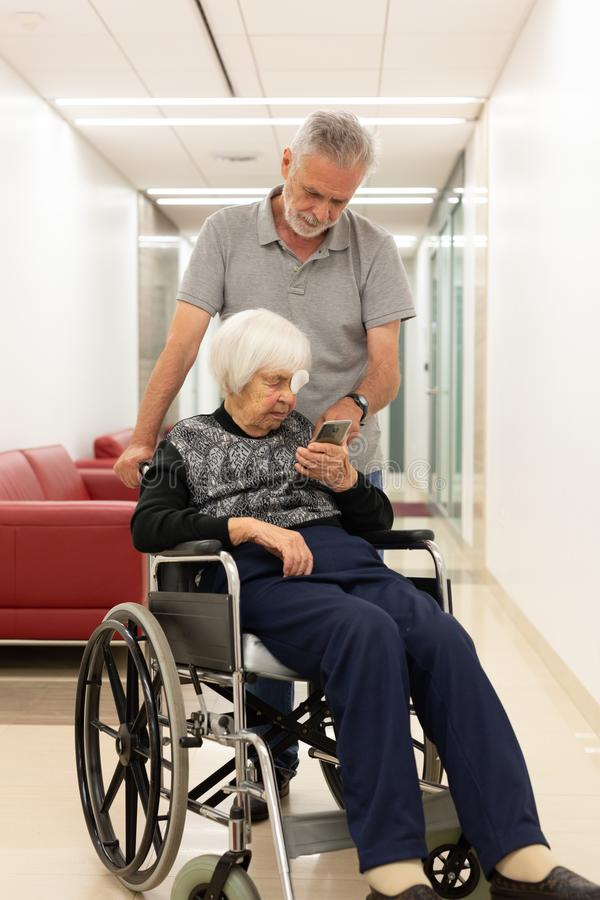 Middle aged man showing and helping elderly 95 years old woman sitting at the wheelchair how to use modern mobile phone. stock photo