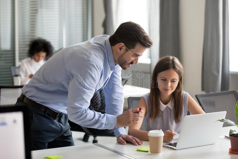 Middle aged mentor explaining online work to young focused inter. Middle-aged executive manager boss mentor teacher explaining online work to young focused royalty free stock photo