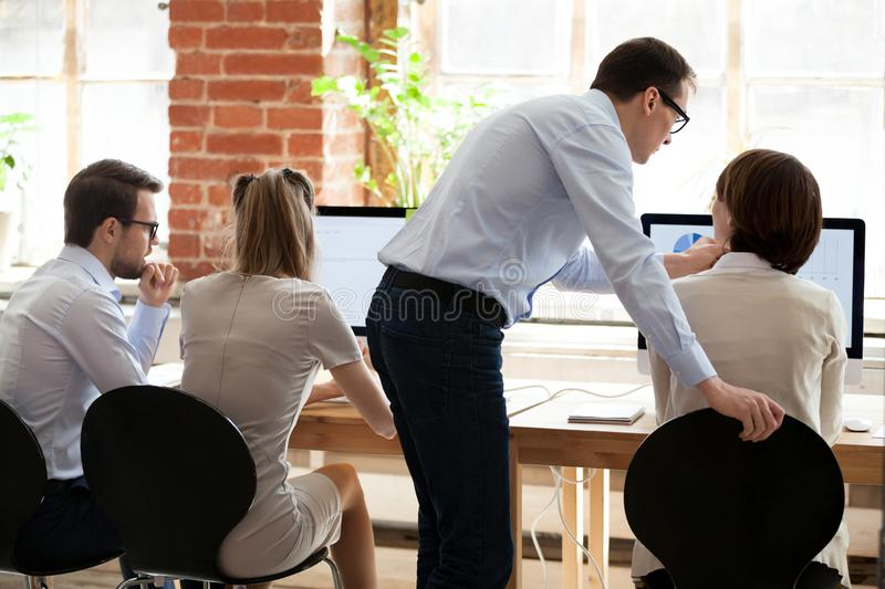 Middle aged mentor helping female employee with computer work. Economic report, presentation with graphics and diagram, boss explaining task to subordinate in stock photo