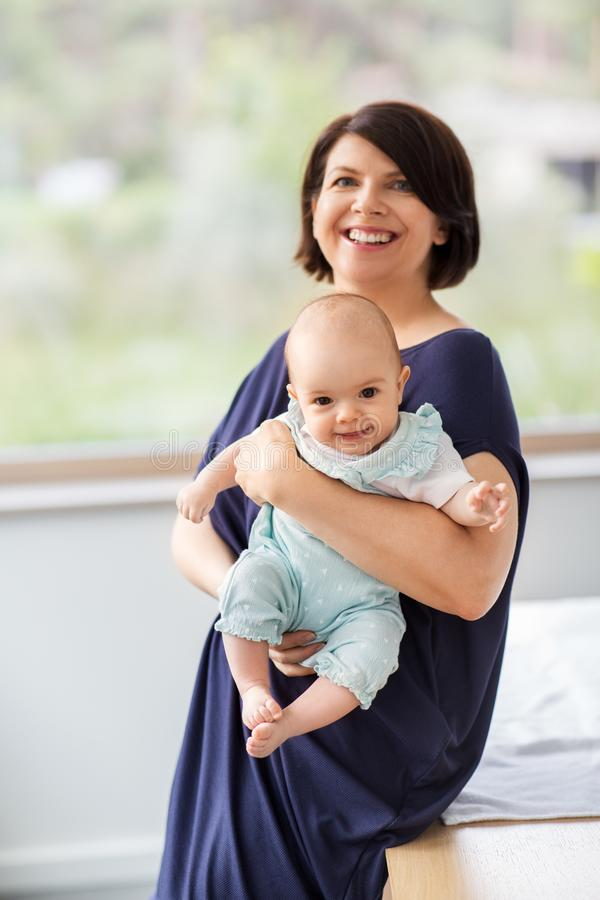 Middle-aged mother holding baby daughter at home stock photography