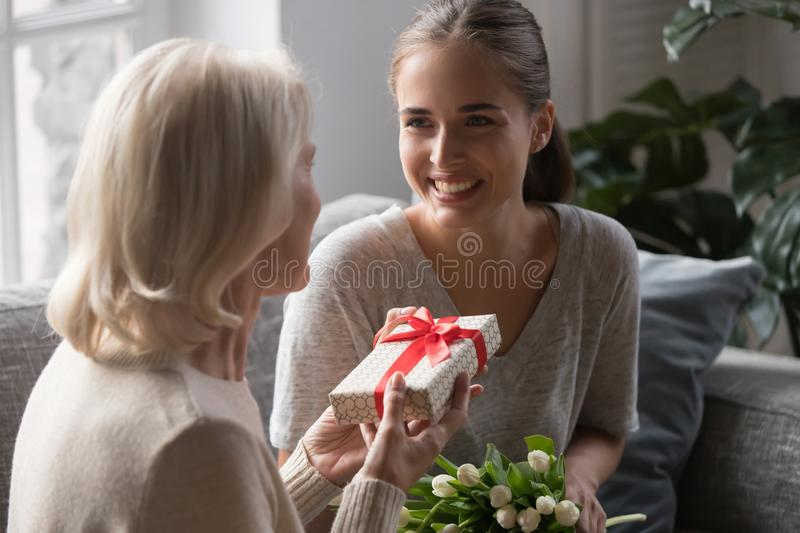 Middle aged mother receiving from grown up daughter gift box stock photos