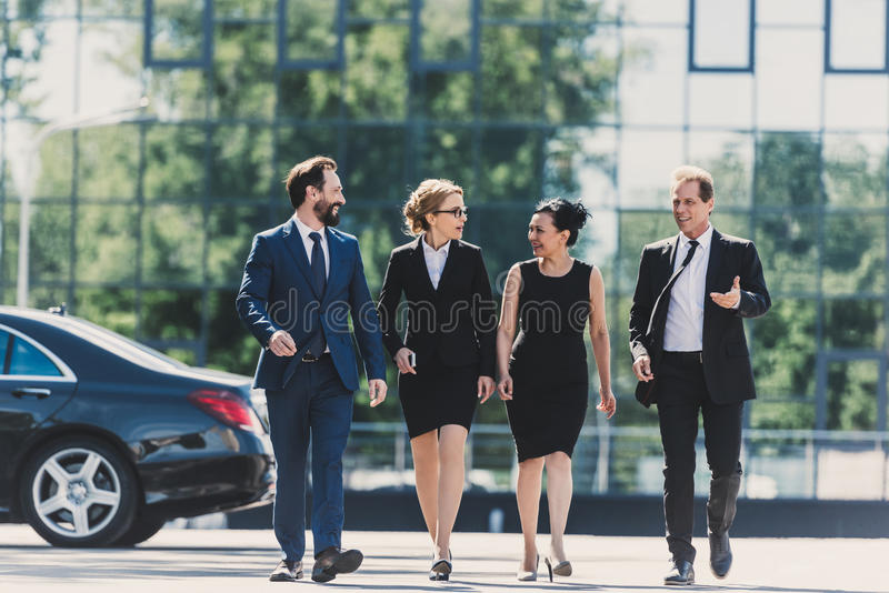 Middle aged multiethnic businesspeople walking together and talking in city stock photos