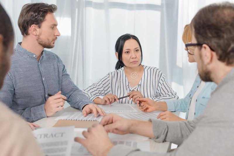middle aged multiethnic people signing contract at anonymous stock photo