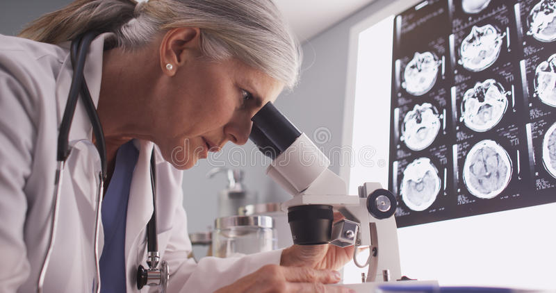 Middle aged neurologist female researching with microscope royalty free stock image