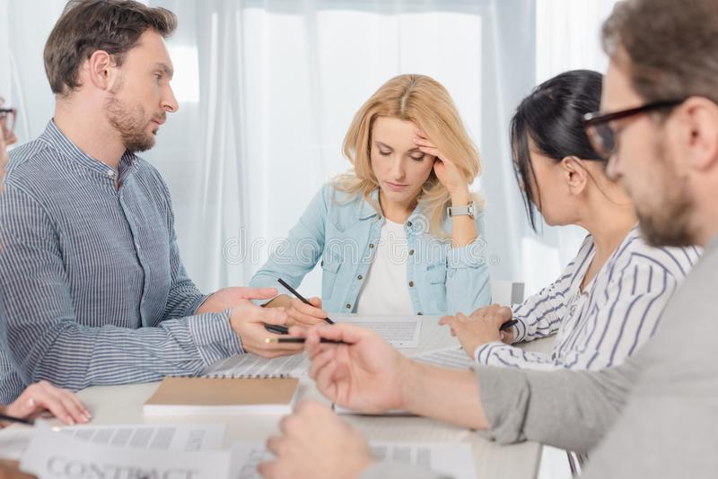 middle aged people signing contract at anonymous stock photo