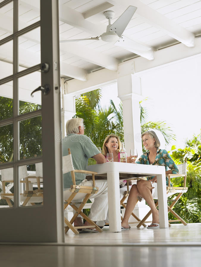 Middle Aged People Sitting At Verandah Table stock image