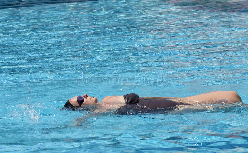 Middle aged pregnant woman swimming in spa pool to relax royalty free stock photography