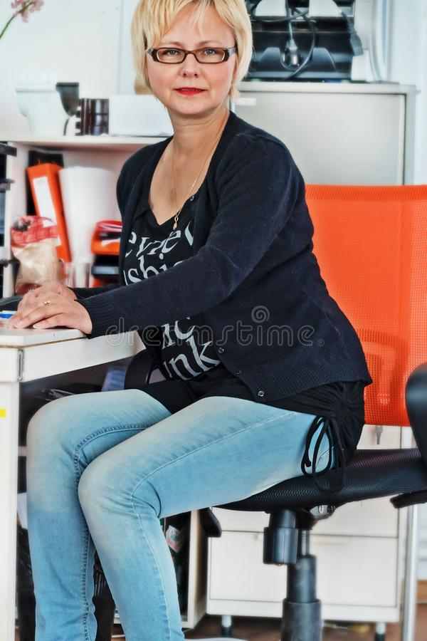 Middle-aged pretty business woman working at pc in office stock photo