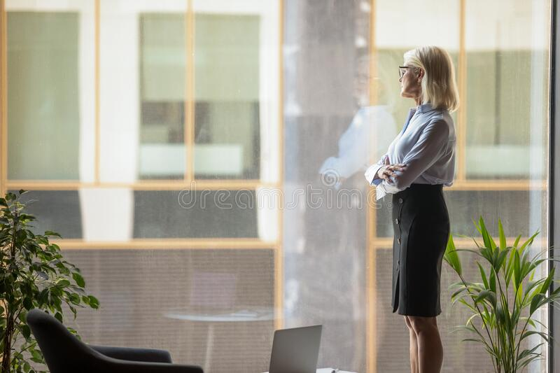 Aged businesswoman looking out window dreaming about corporate goals realizations royalty free stock image