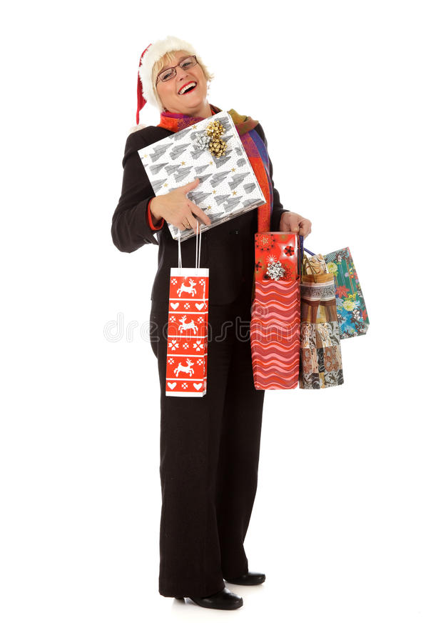 Middle aged santa woman, many gifts. Cheerful Caucasian middle aged woman with Santa hat, carrying box and many shopping bags with gifts for Christmas . Studio stock photography