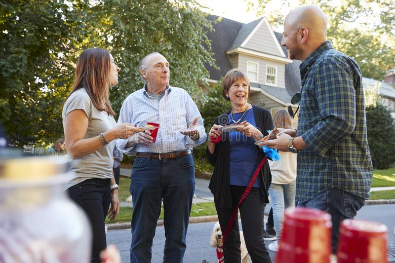 Middle aged and senior neighbours talking at a block party stock image