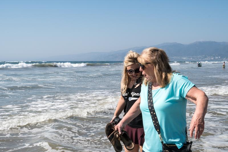 Middle aged senior woman in her 60s walks along the shoreline in Santa Monica California with her blonde adult daughter royalty free stock images