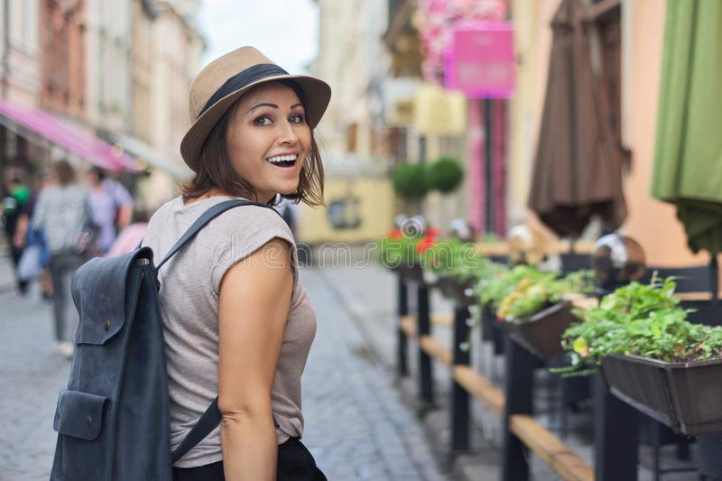 Middle aged smiling woman in hat traveling in tourist city royalty free stock photos
