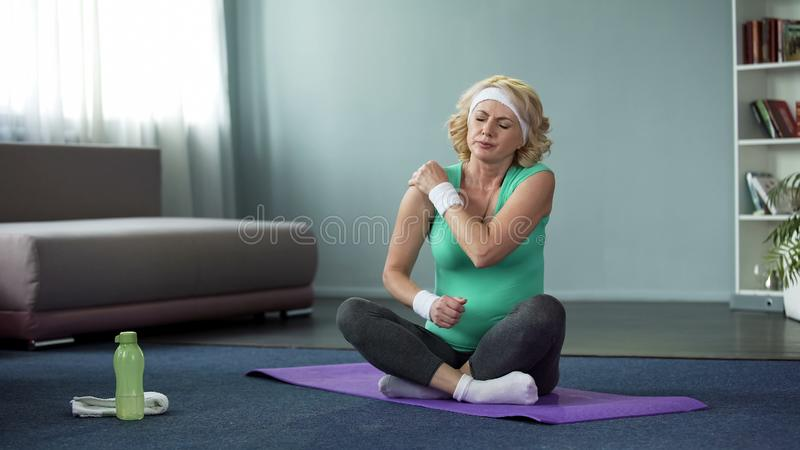 Middle-aged sport woman feeling shoulder pain after workout, joint inflammation stock photography
