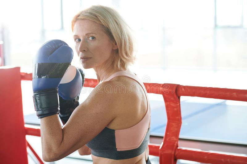 Strong woman. Middle aged sporty female with blonde hair looking at you while holding her hands in boxing gloves in front of face royalty free stock photo