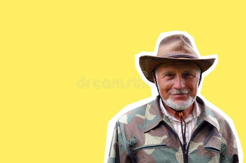 Middle aged traveler. Portrait of a handsome adult man with a gray beard and hat in camouflage clothing royalty free stock images