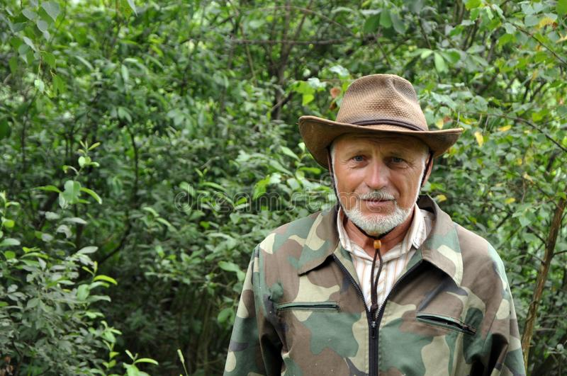 Middle aged traveler. Portrait of a handsome adult man with a gray beard and hat in camouflage clothing stock photos