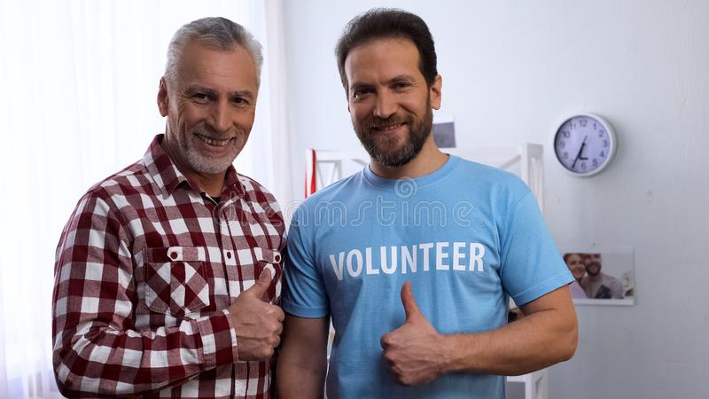 Middle-aged volunteer and elderly man showing thumbs-up at camera, caregiver stock photos