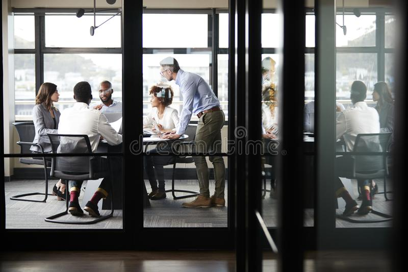Middle aged white businessman stands addressing colleagues at meeting, seen through glass wall stock images