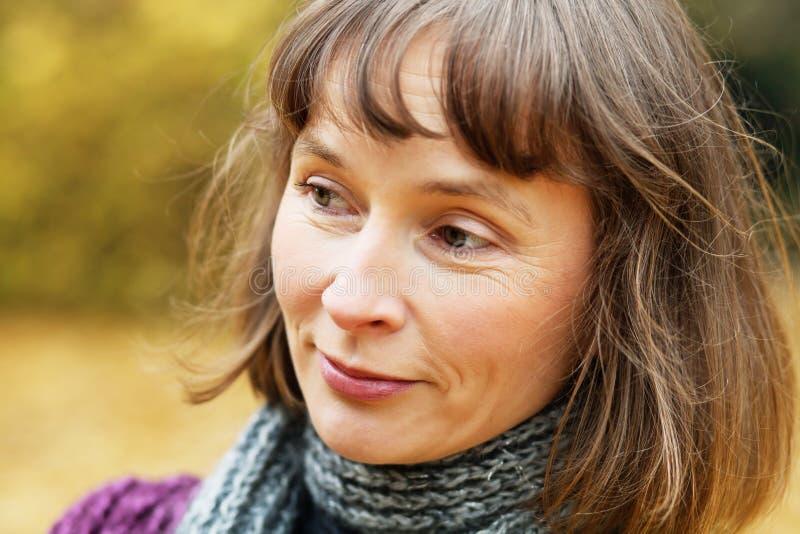 Middle aged woman in autumn park. Portrait of cheerful middle aged woman in an autumn park stock photos