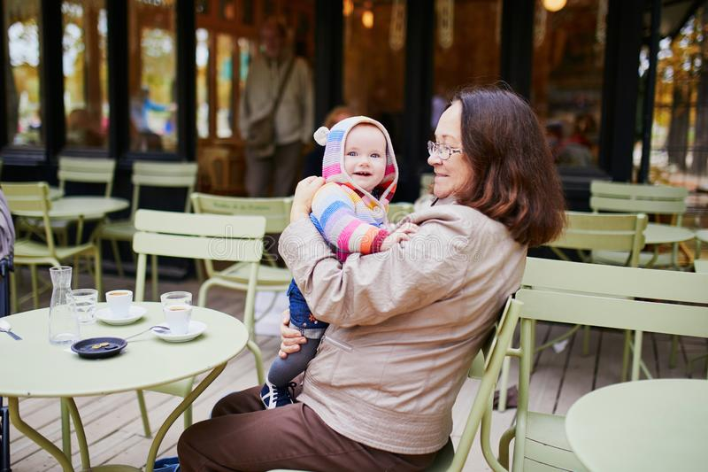 Middle aged woman with baby girl in Parisian outdoor cafe royalty free stock photos