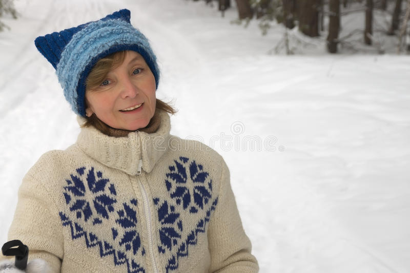 Middle-aged woman in the background of a winter fo. Middle-aged woman smiling with pleasure skiing royalty free stock images