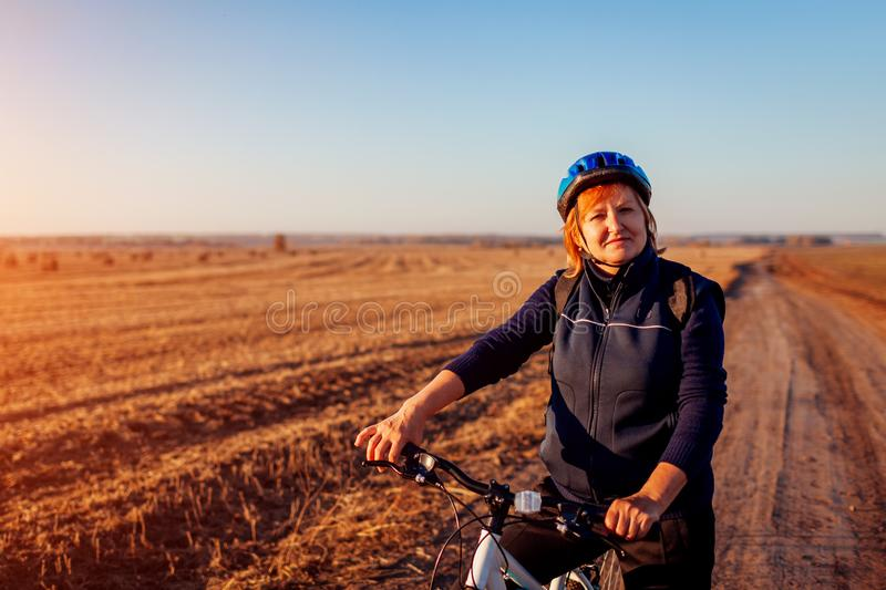Middle-aged woman bicyclist riding in autumn field at sunset. Senior sportswoman enjoying hobby. royalty free stock photography