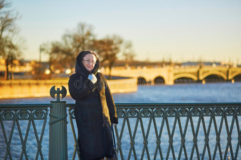Middle aged woman on the bridge in St. Petersburg, Russia on a sunny winter day. Smiling middle aged woman on the bridge in St. Petersburg, Russia on a sunny stock photo