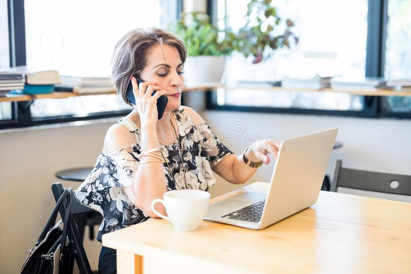 Middle aged woman busy working at cafe royalty free stock image
