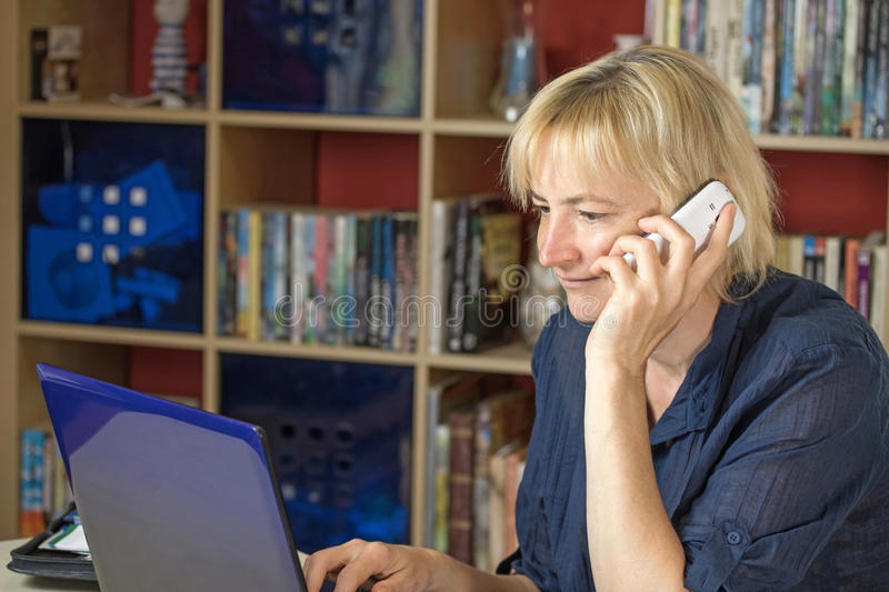 The middle aged woman is calling a mobile phone. The middle aged blonde woman is smiling and calling a mobile phone. At the same time it is looking into the stock images