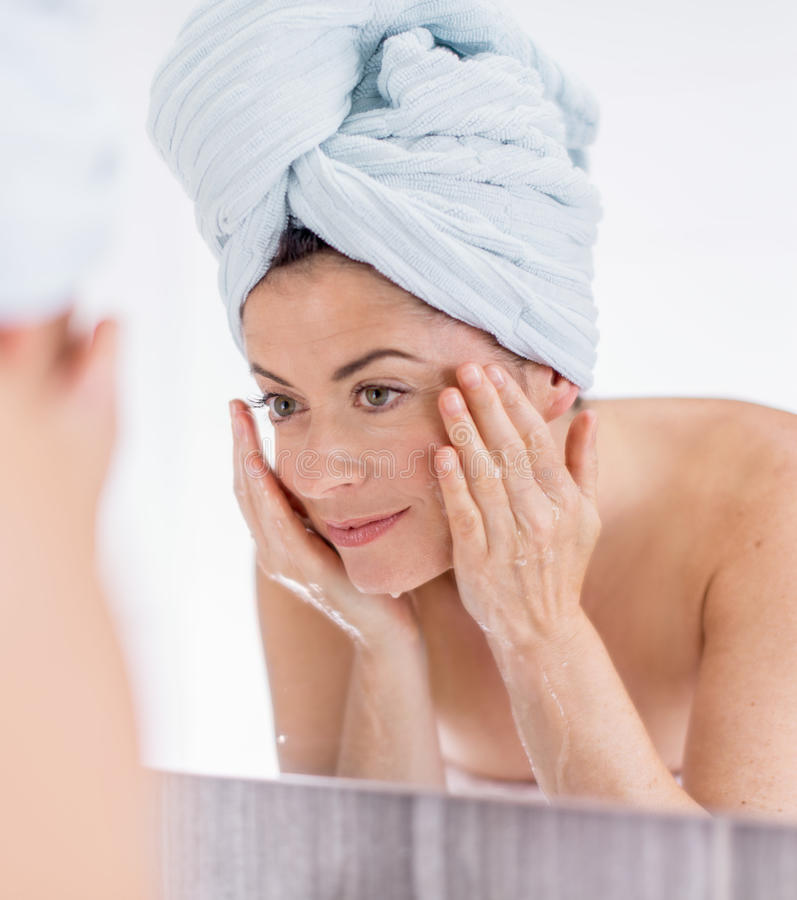 Middle aged woman cleaning her sking over the sink. Mature lady using soap and water to purify her skin stock photography